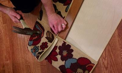 Woman hammering tack nails into board to secure a flowered area rug to wood for cat