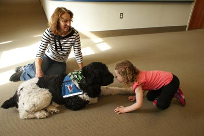Laure Seiber and her therapy dog Charlie work with a child at the Barber National Institute in Erie, Pa.