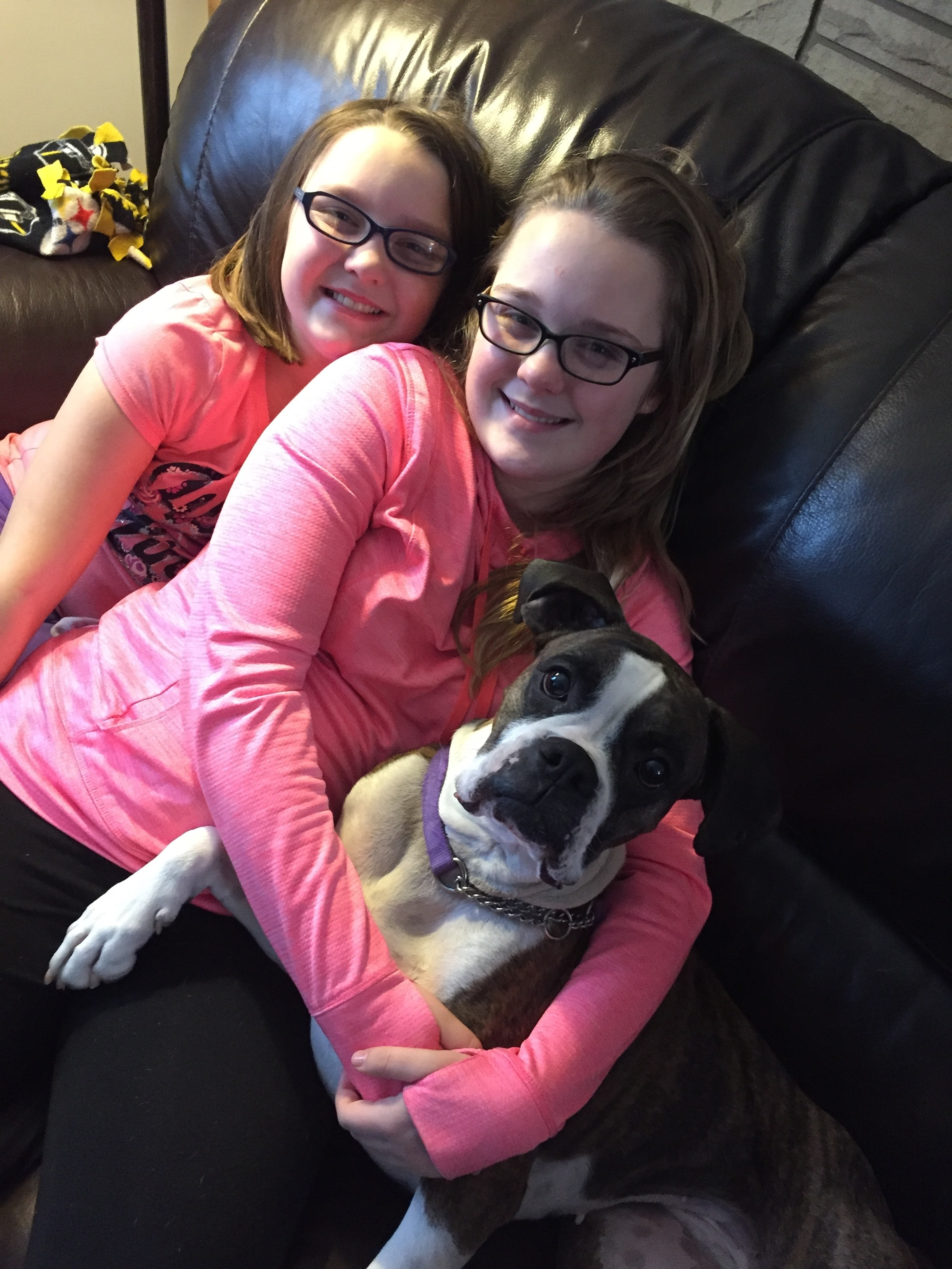 Two girls in pink on a couch sit hugging a black and white boxer.