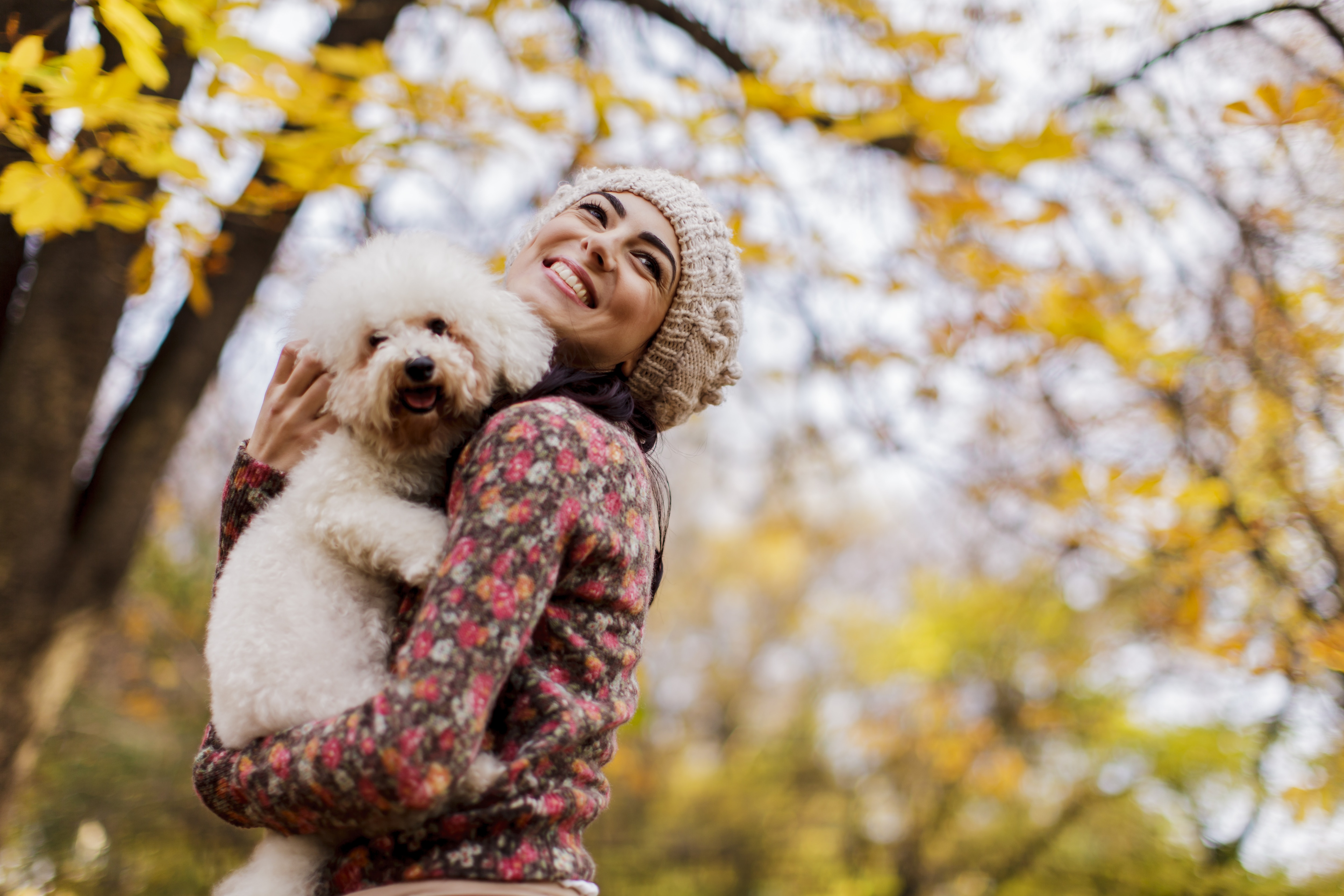 Brunette woman in knitted beanie and flowered shirt holds a shaggy dog with fall trees in background.