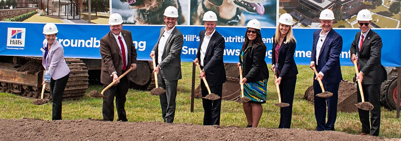 Group of people wearing hard hats with shovels at a groundbreaking ceremony for Hill's Pet Nutrition.